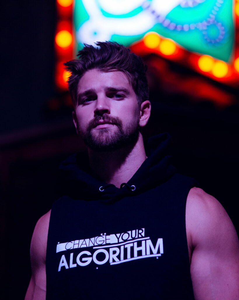 Cole in Sleeveless Change Your Algorithm shirt under neon lights
