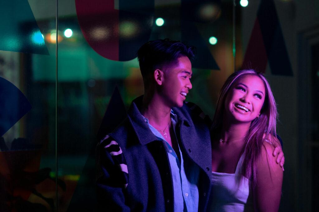Luke and Britney smiling under neon lights