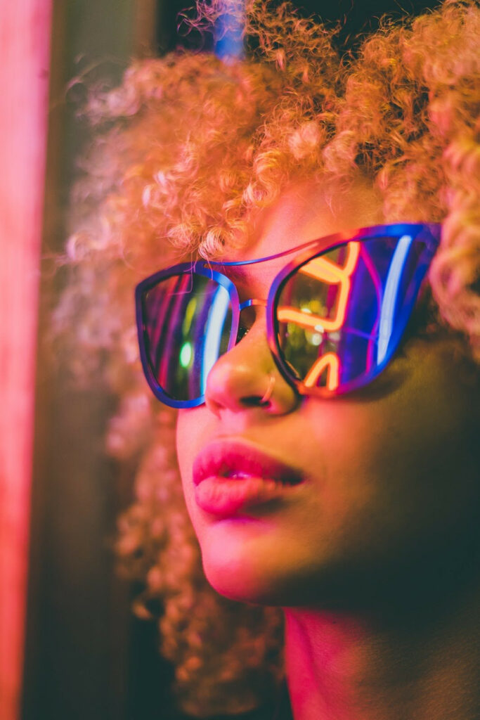 wearing sunglasses, neon lights reflected on glasses