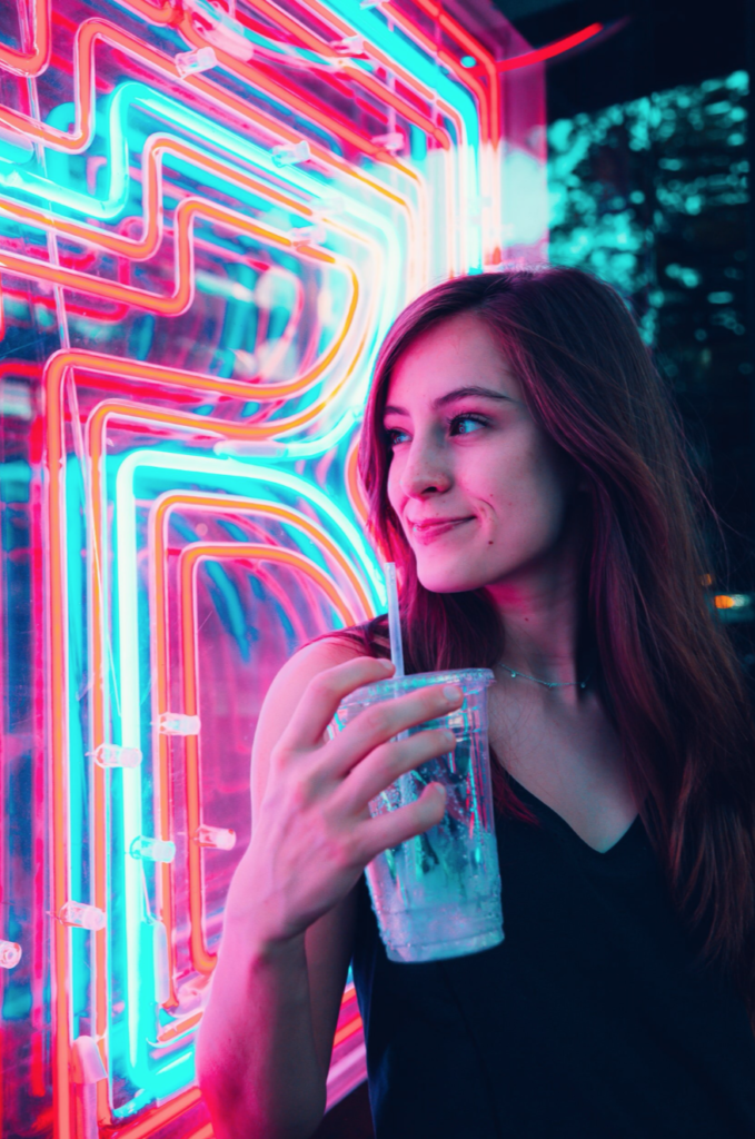 smiling woman next to neon sign